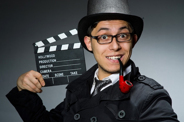 Detective in black coat with clapperboard against gray