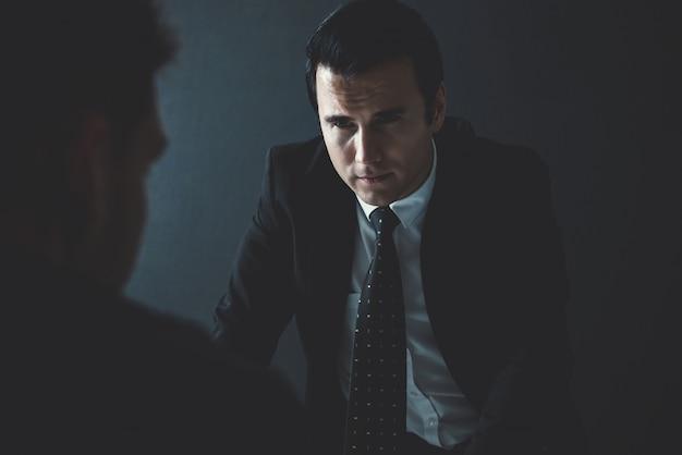 Detective interviewing criminal man in interrogation room