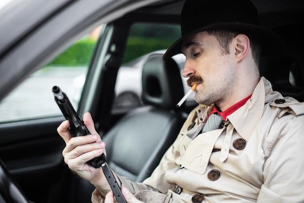 Детектив готовит пистолет, ожидая в своей машине