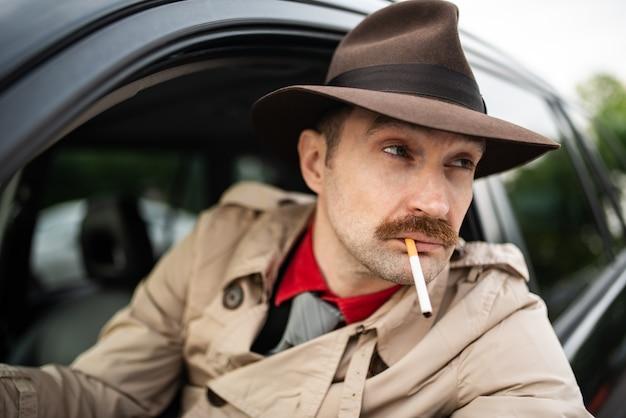 ストーカーをしながら車の中でタバコを吸う探偵
