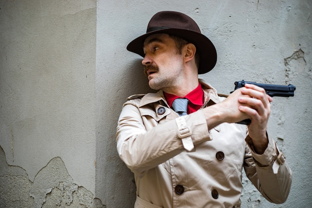 Detective taking cover and aiming with his handgun