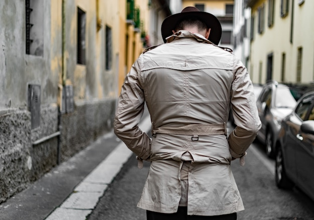 Detective walking in the city slums, view from the back