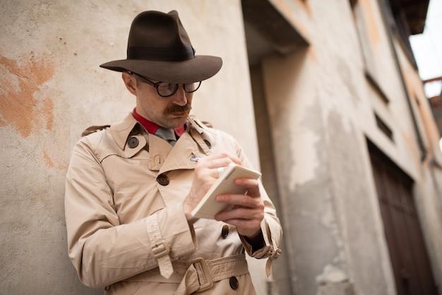 Детектив пишет в блокноте, стоя у старой стены