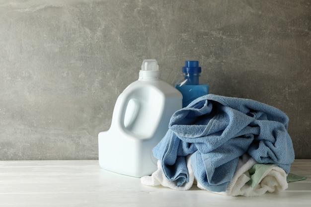 Моющее средство и мятые полотенца на сером фоне