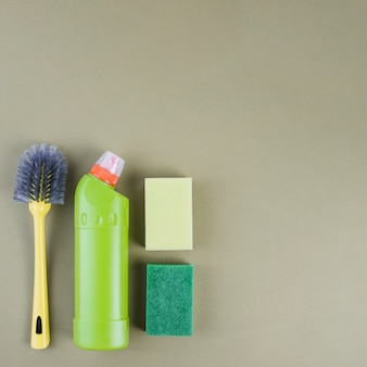 Бутылка моющего средства, кисть и губка на цветном фоне