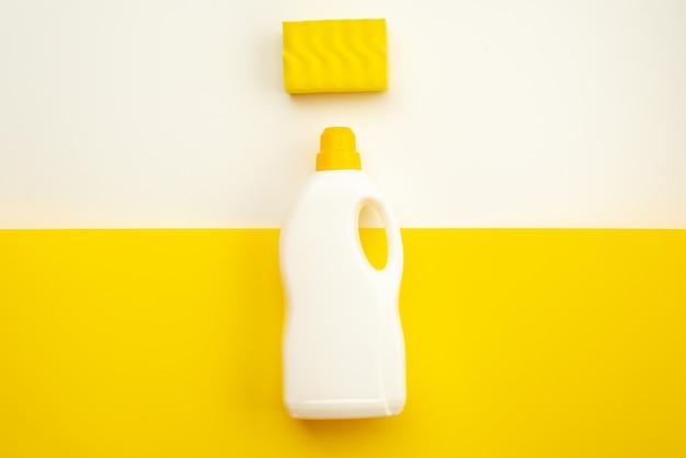 黄色のキャップとスポンジが白黄色のテーブルの上にある洗剤ボトル