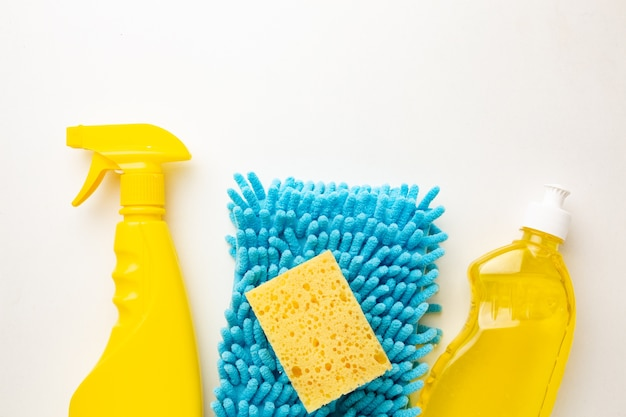 洗剤のボトルと白、フラットレイアウトに分離された青いスポンジ