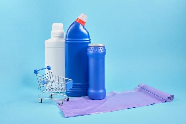 Пластиковый пакет для бутылок с моющим средством для мусора и тележки для покупок на синем фоне с копией пространства