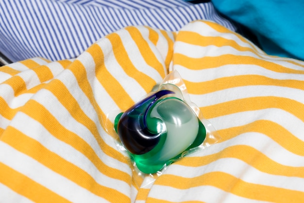Detergent pods a means for washing and removing stains lies on a pile f laundry