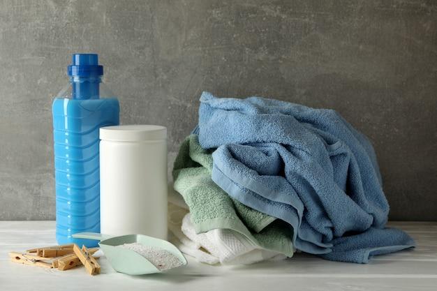 Моющее средство, порошок и полотенца на деревянном столе против серого
