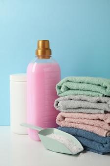 Моющее средство, совок с порошком и полотенца на белом столе против синего стола