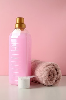 Detergent, scoop with powder and towel on white table against pink background