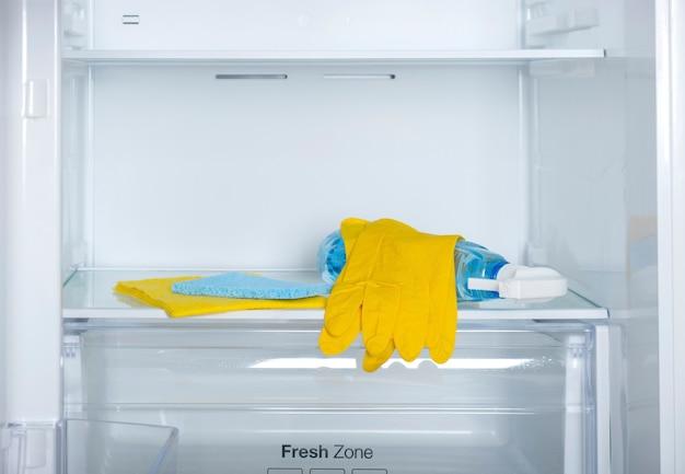 세제 노란색 고무 보호 장갑과 파란색 스폰지가 냉장고 선반을 세척하고 청소합니다.