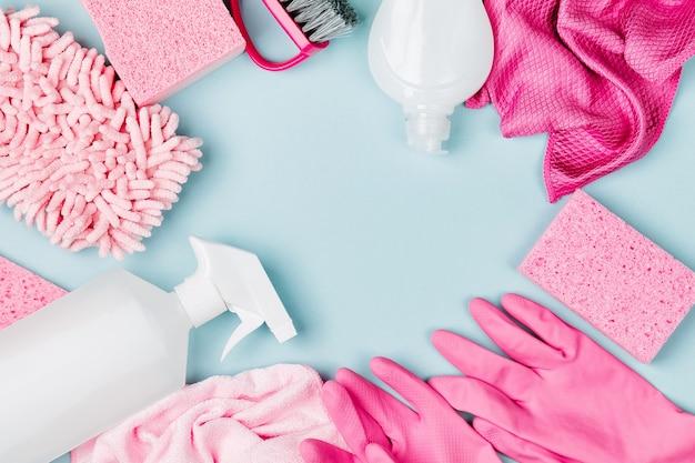 ピンク色の洗剤とクリーニングアクセサリー。クリーニングサービスのコンセプト。フラットレイ、上面図。