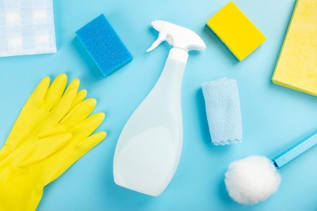 Моющие и чистящие средства, губки, салфетки и резиновые перчатки, синий фон. вид сверху