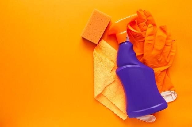 洗剤、洗浄剤、スポンジ、ナプキン、ゴム手袋、オレンジ色の背景。上面図。コピースペース