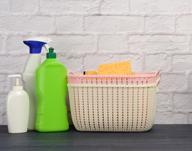 Detergents in plastic bottles and baskets on white brick wall surface