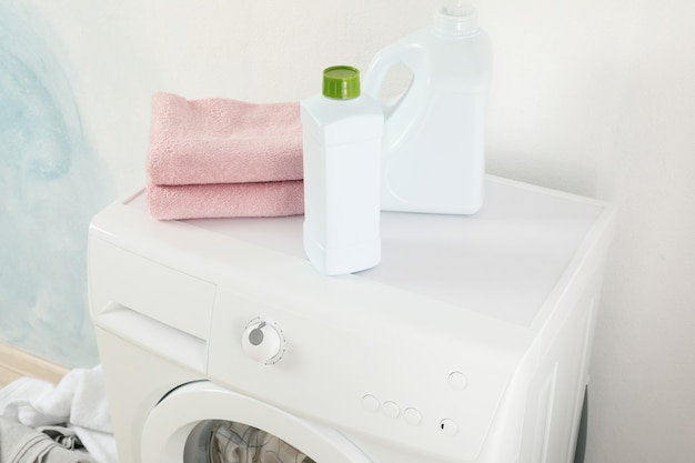 Detergents and towels on washing machine, close up