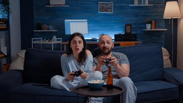 Решительная взволнованная пара, выигравшая видеоигры, обняла друг друга, сидя на диване и играя в счастье ...