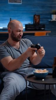 ビデオゲームをしているソファに座っている決心した興奮した男は、オンライン競争を楽しんで幸せの叫び声を上げます...