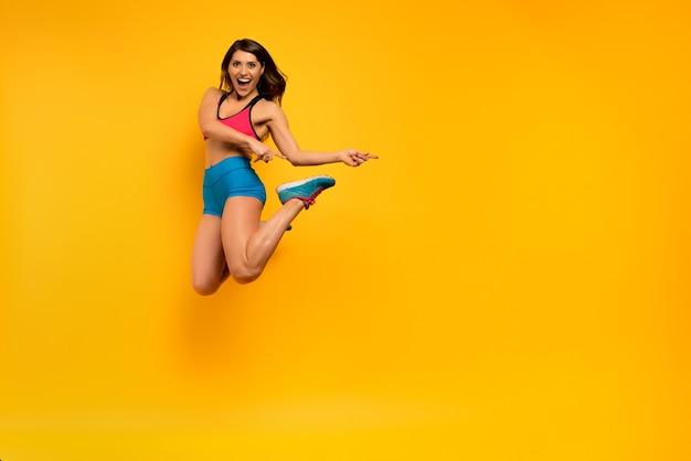 決定されたスポーツの女性は黄色の背景にジャンプします