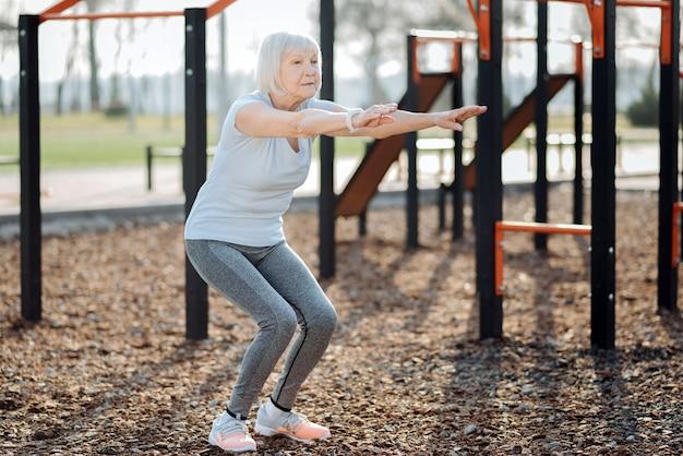 Определение. сосредоточенная пожилая женщина делает приседания и тренируется на свежем воздухе