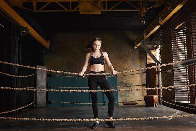 決意、持久力、強さの概念。黒のスニーカー、トップス、レギンスを身に着けているスタイリッシュな若い白人女性キックボクサーのフルレングスショット