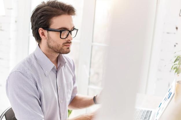 決定。テーブルに座って彼のラップトップで作業しているプロのひげを生やしたマネージャー