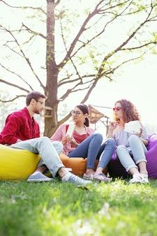 Определение. серьезная красивая женщина сидит на открытом воздухе со своими коллегами и обсуждает свой проект