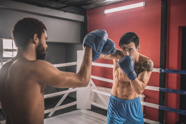 Determination. young men fighting on a boxing ring and looking determined
