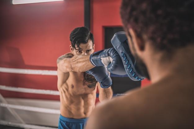 Определение. молодые люди борются на боксерском ринге и выглядят решительно