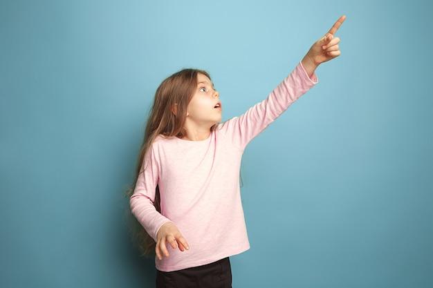 Determinazione e scelta. ragazza teenager seria sul dito rivolto verso l'alto blu. le espressioni facciali e le emozioni delle persone concetto