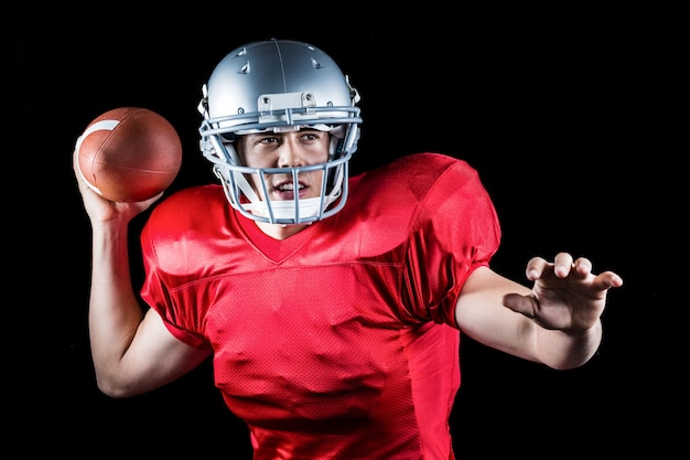 Determined american football player throwing ball