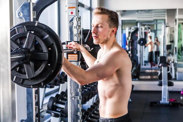 단호하고 강한 피트니스 남자는 피트니스 클럽에서 무거운 무게로 훈련을 준비합니다. 매력적인 근육 질의 남자 선수 체육관에서 무거운 무게 역기와 함께 밖으로 작동합니다.