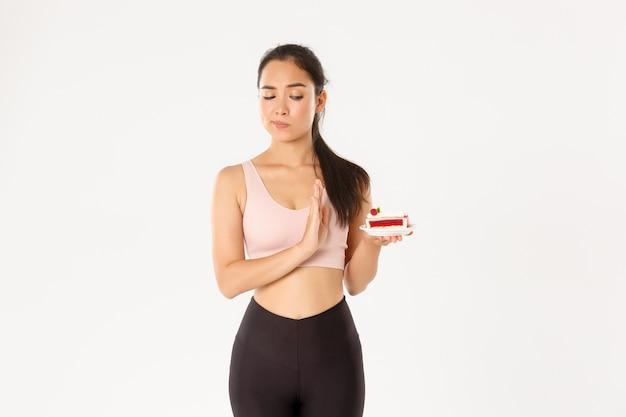 お菓子を拒否し、ダイエット中にジャンクフードを食べるのをやめ、体重を減らし、ケーキを食べることを拒否し、嫌がる白い背景に立っているアジアの女の子アスリートを決定しました。