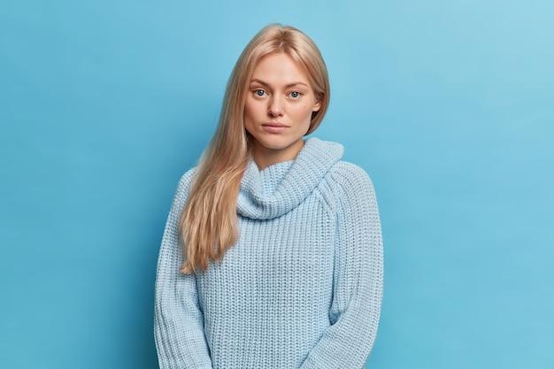 Determinata e assertiva giovane donna europea bionda guarda seriamente, vestita con un maglione lavorato a maglia