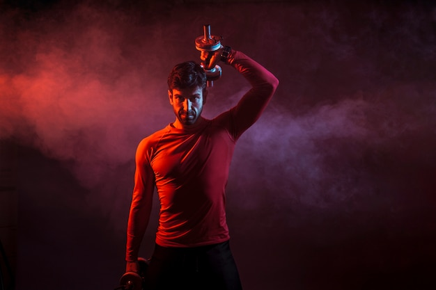 Determined athlete with dumbbells in dark