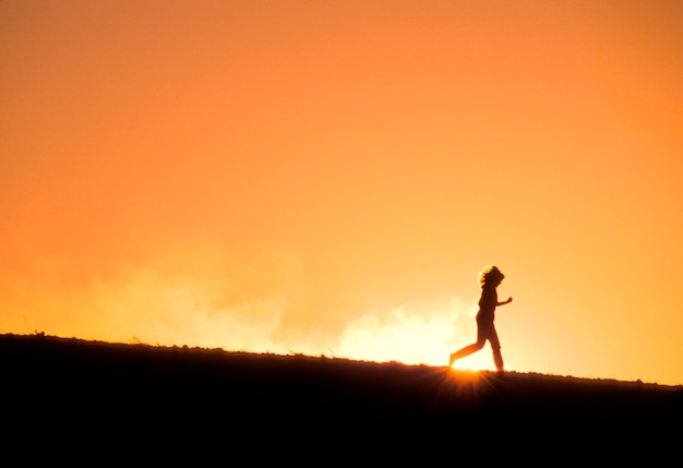 Determined, athletic runner running downhill against sunset in remote area