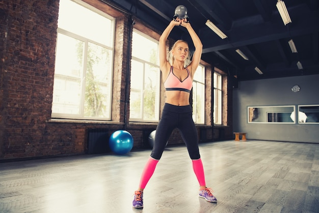 Determined blonde girl working out at the gym with a kettlebell