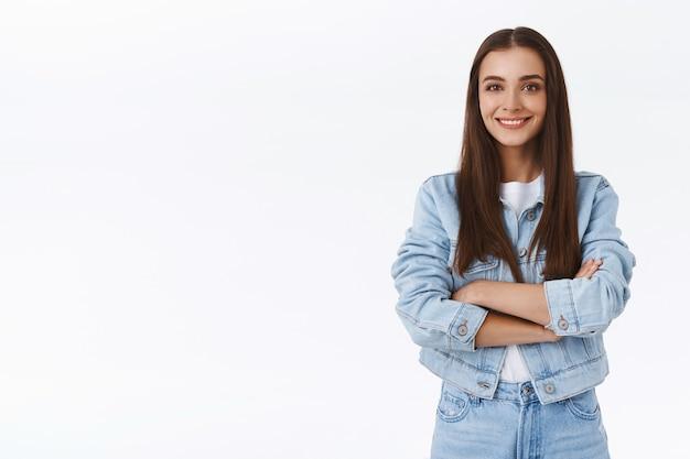 Determinata, fiduciosa, felice ragazza bruna in giacca di jeans, jeans, braccia incrociate sul petto, sorridente ottimista, dall'aspetto assertivo, sicuro di sé, in piedi spensierato su sfondo bianco con un sorriso amichevole