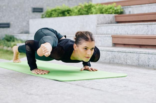 Решительная женщина с гибкой посадкой кладет ногу на руку, делая планку на коврике для йоги