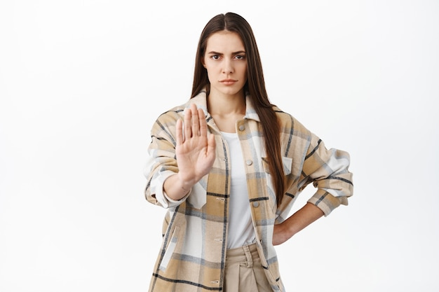 Determined frowning woman stretch hand in stop, block gesture, say no, keep social distance during pandemic, dont come close, refuse or prohibit something, disagree, white wall