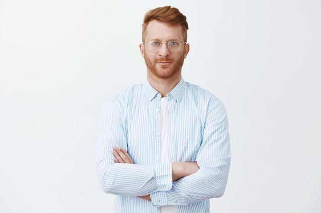 眼鏡とシャツを着た見栄えの良いきちんとした男性の赤毛を決定し、自信を持って胸に手を組んで、見て、注意深く耳を傾けます