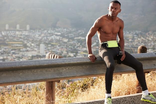 決心した男性のジョガーは山に向かって走り、レギンスとトレーナーを着て、彼の筋肉の体を表し、水のボトルを運び、脇を向いています。あなたの情報やスローガンのための空白のコピースペース