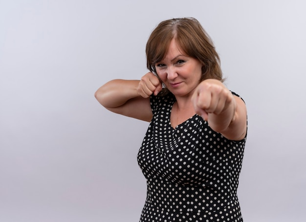 Determinata donna di mezza età che fa il gesto del pugno sulla parete bianca isolata