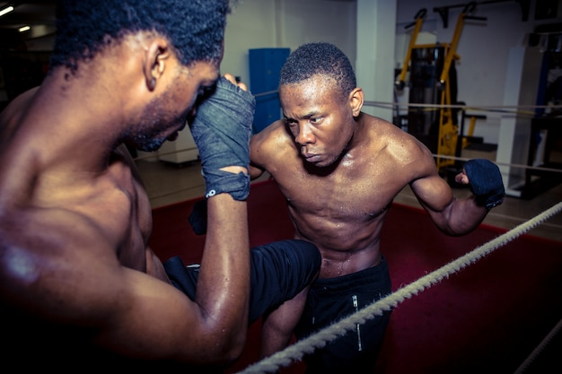 Determined offensive fighter hitting his opponent while practici