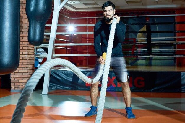 Решительный спортсмен работает с веревками