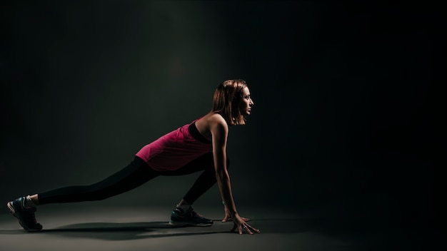 Determined sportswoman stretching on black