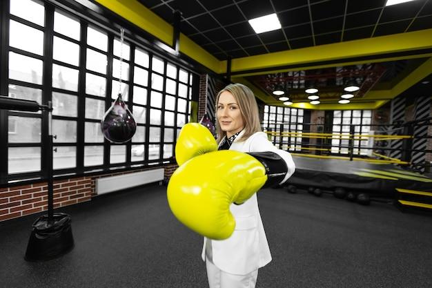 Решительная стильная бизнес-леди в желтых боксерских перчатках наносит удар в камеру на фоне боксерского ринга.