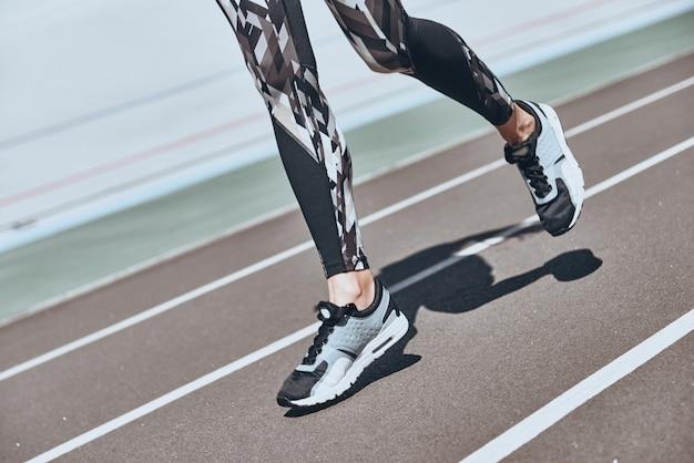 Решительно настроен на победу. заделывают молодой женщины в спортивной обуви, бегающей трусцой